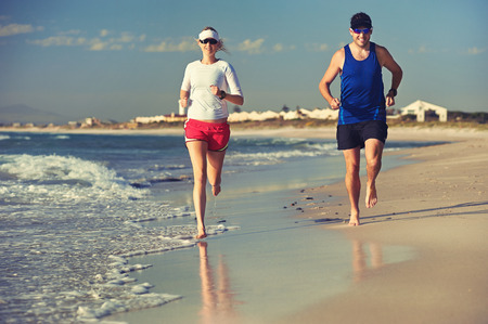 couple running barefoot on beach at sunset for healthy lifestyle photo