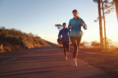 Running at sunrise couple exercising for marathon and workout fitness photo