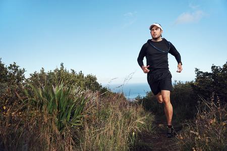 mountainn トレイル マラソンのトレーニングのため海の運動に近い男を実行しているフィットネス 写真素材