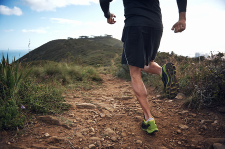 tough: trail running athlete exercising for fitness and health outdoors on mountain pathway