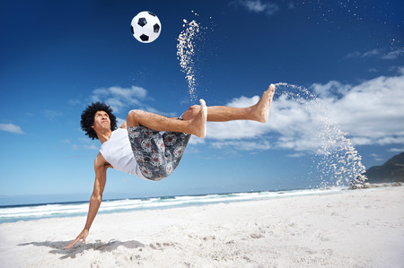 Latino Hispanic man doing bicycle kick on beach with soccer ball