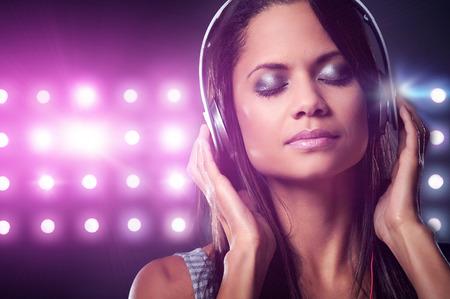 Portrait of woman dj enjoying music on headphones and nightclub lights photo