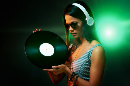 Woman dj portrait with vinyl record and headphones photo