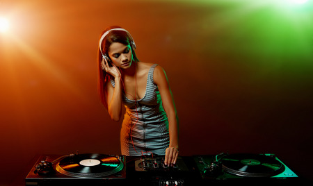 real woman dj playing music at party photo