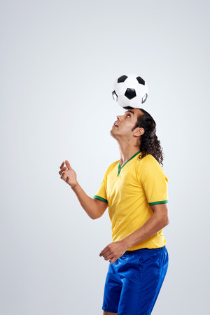 other world: football player ballancing soccer ball on head in display of skill