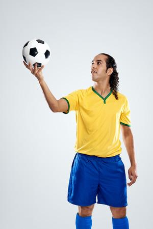 other world: football player spinning ball on finger wearing full brasil kit for world cup soccer brazil