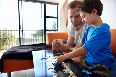 Father and son building puzzles together photo
