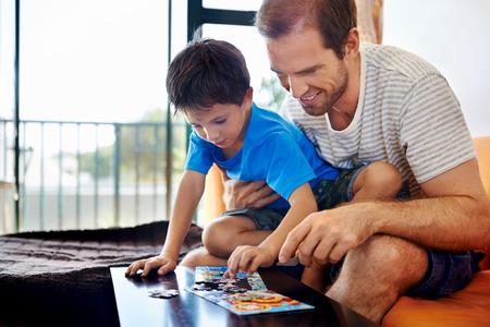 笑みを浮かべてお父さんと息子が一緒にパズルを構築 写真素材
