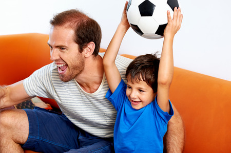 watching football: father and son soccer fans cheering with football ball