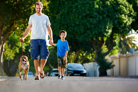 A father walking with his dog and his son in the suburbs Stock Photo