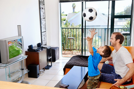 involved: Father and son watching football cup soccer on tv together in living room on sofa being excited fans