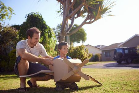 piloto de avion: hijo y papá jugando con avión de juguete en el jardín en casa teniendo diversión juntos y sonrientes