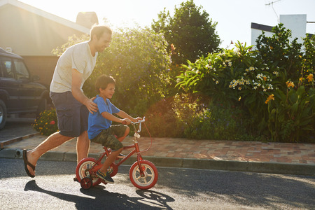 cycle ride: young boy learning to ride bicycle as father teaches him in the suburb street having fun. Stock Photo
