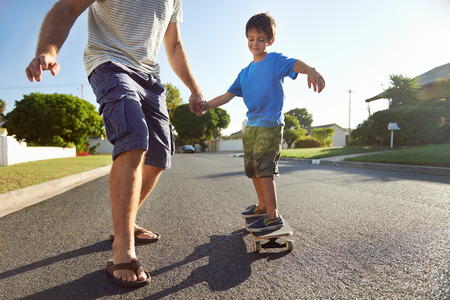 teaching children: young boy learning to ride skateboard as father teaches him in the suburb street having fun.