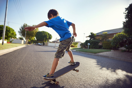 neighbourhood: young boy learning to ride skateboard in the suburb street having fun.