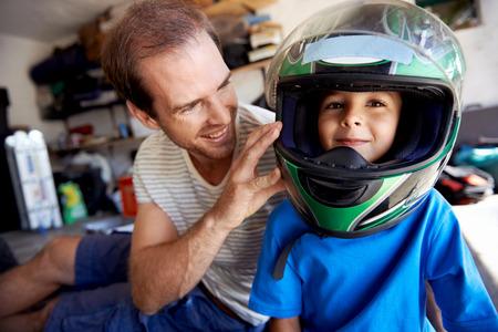 casco de moto: retrato de un niño pequeño jugando con el casco de moto padres y ayudando a su padre con la fijación de una motocicleta en el garaje Foto de archivo