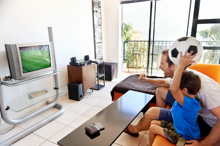 Father and son watching football cup soccer on tv together in living room on sofa being excited fans