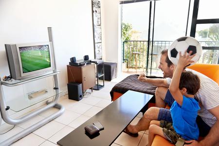 Padre e hijo que ven la taza del fútbol del fútbol en televisión juntos en la sala de estar en el sofá siendo fans emocionados