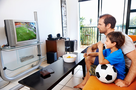 Father and son watching football cup soccer on tv together in living room on sofa being excited fans photo