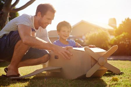 piloto: hijo y papá jugando con avión de juguete en el jardín en casa teniendo diversión juntos y sonrientes