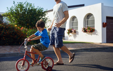 neighbourhood: young boy learning to ride bicycle as father teaches him in the suburb street having fun. Stock Photo
