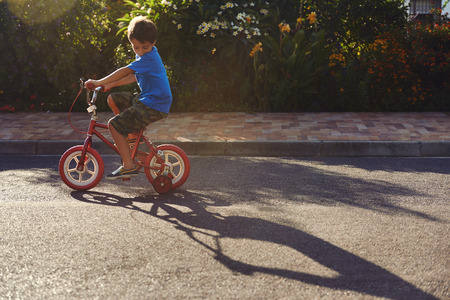 training wheels: young boy learning to ride bicycle with training wheels at sunset