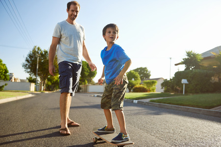 neighbourhood: young boy learning to ride skateboard as father teaches him in the suburb street having fun.