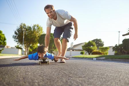 Mladý chlapec se učí jezdit na skateboardu, jak jej otec učí na předměstí ulici baví.