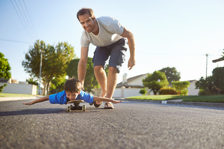 skateboarding: young boy learning to ride skateboard as father teaches him in the suburb street having fun.