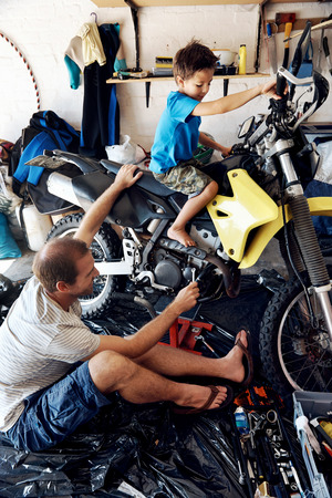 A boy helping his dad with fixing a motorcycle in the garage