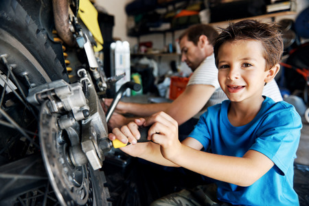 portrait of a boy helping his dad with fixing a motorcycle in the garage