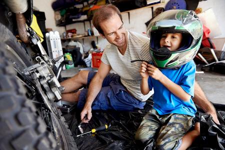 portrét mladého chlapce, jak hraje s otcové motorce helmu a pomáhal jeho otec s upevnění na motocyklu v garáži