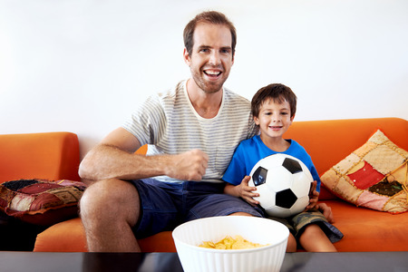 bonding: Father and son watching football cup soccer on tv together in living room on sofa being excited fans