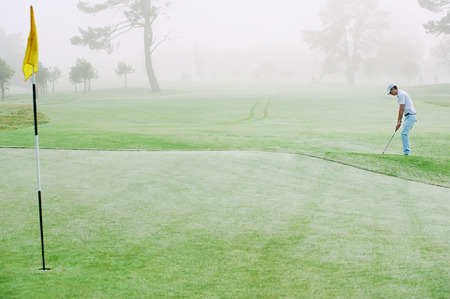 霧深い条件でゴルフコースの日の出、グリーンにチッピングのゴルファー
