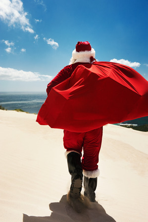 christmas in july: Back-view of Santa Claus walking along a beach holding a sack full of presents Stock Photo