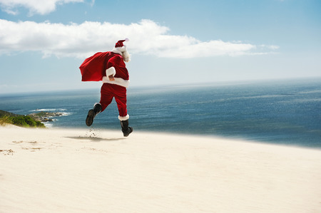 christmas in july: Father Christmas walking along the beach with copyspace Stock Photo
