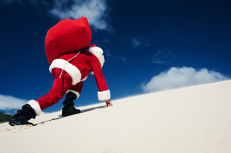 Father Christmas on the beach climbing up a sand dune with copyspace Stock Photo - 29194692