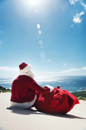 christmas in july: Man in Santa costume sitting on a beach looking at view