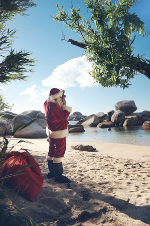 Santa Claus standing on a beach taking a picture of the view Stock Photo - 29194698