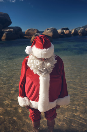 Man in a Santa Claus costume with his bare feet in the calm water of a beach Stock Photo - 29194699