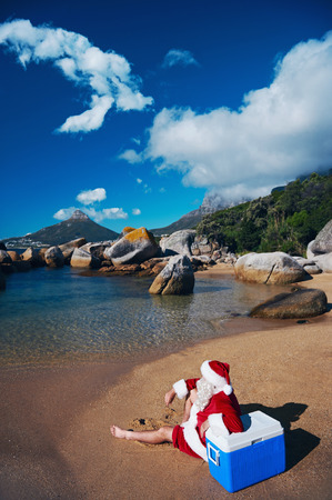 Santa Claus relaxing on the beach looking at the view leaning on his Cooler
