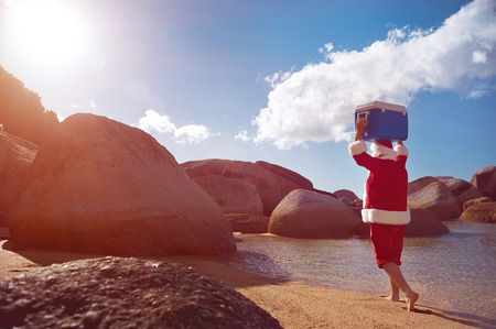 Man in Santa Claus costume walking along the beach with his Cooler on his head with copyspace Stock Photo