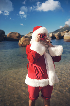 Santa Claus on a beach taking a picture with a quirky camera while he has his feet in the water of a beach Stock Photo - 29194712