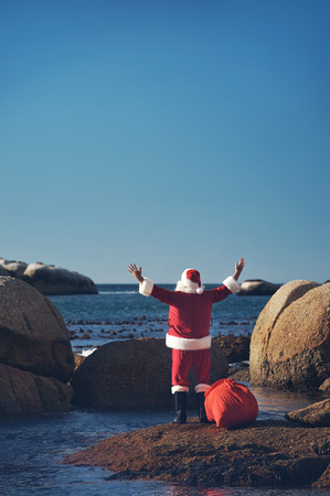 Back view shot of Santa Claus enjoying the seas air with his hands raised looking over the ocean with copyspace Stock Photo - 29194713