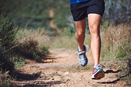 stride: Trail running man exercising outdoors for fitness