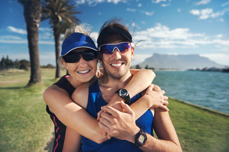 hugging couple: Happy fitness couple portrait while training in the park for marathon run