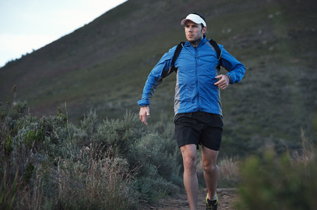 ultra: ultra marathon trail runner training in mountains for fitness and exercise wearing  Stock Photo