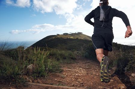 山のパスを行使を走っている男をトレイルします。