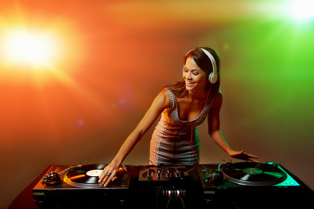 Cute dj woman having fun playing music on vinyl record deck at club party nightlife lifestyle photo
