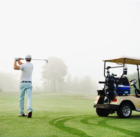 golfer in fairway with cart playing shot towards green photo